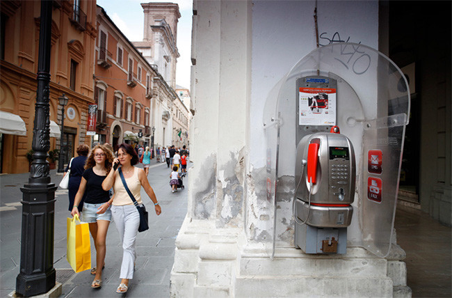 Pedestrians walk past a fixed-line public telephone booth, operated by Telecom Italia SpA, in Chieti, Italy, on Aug. 28, 2014. Photographer: Marc Hill/Bloomberg.